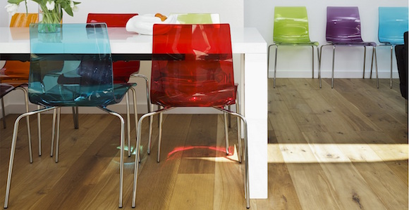 Colourful plastic chairs at white dining table opposite modern artworks on wall