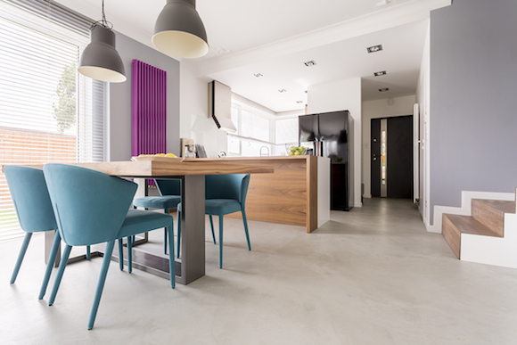 Monochromatic modern open plan apartment with colorful and wooden accents in dining room and kitchen with stairs and door entrance