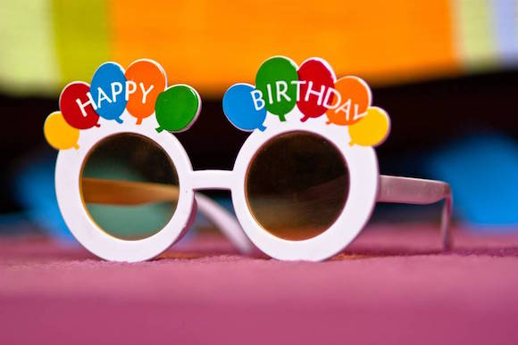 funky birthday glasses on colored background